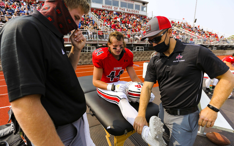 Athletic trainers assisting football player
