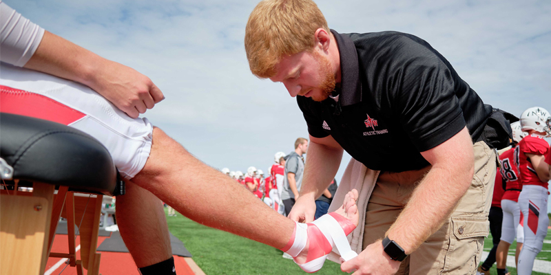 Athletic training student taping a football player's ankel